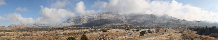 Clouds over the Sandias panorama. True wide panorama of the heavy clouds of the first snowstorm of the winter hovering over the Sandia Mountains near Albuquerque Stock Photo