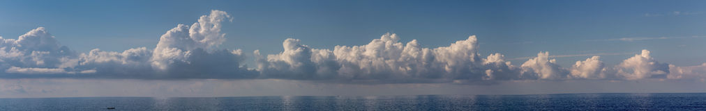 Clouds over the sea. Blue skyline over the sea with long clouds stock photo