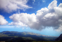 Clouds over sea coast. A kind from mountain. Stock Photo