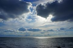 Clouds over the sea. Storm clouds over the sea the evening, the light of the sun through the clouds Stock Image
