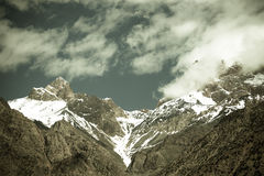 Clouds over the snow-covered tops of the rocks. Landscape. Toned.  Stock Photo