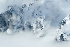 Clouds over snowy mountains Royalty Free Stock Images