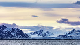 Clouds over snowy mountains and glacier in the arctic Royalty Free Stock Images
