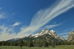 Clouds Over Snowy Peak. Wispy clouds over a mountain peak Stock Photos