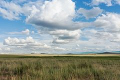Clouds over steppe grass. Tyva. Steppe. Sunny summer day. Outdoors Stock Photos