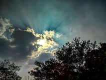 Clouds over the sun in the blue sky stock photography