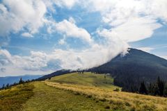 Clouds over top of a mountain with green forest and grass meadow Stock Images