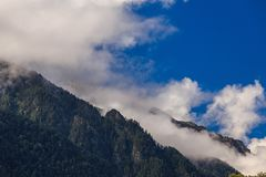 Clouds over the tops of the rocky mountains overgrown with trees royalty free stock image
