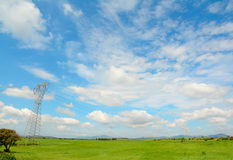 Clouds over a transmission tower. Transmission tower in the countryside under a blue sky royalty free stock photo