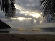 Dark clouds over a beautiful tropical beach with palm trees on Tioman island in Malaysia. Clouds over a tropical beach with palm trees on Tioman island in Royalty Free Stock Photo