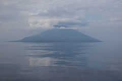 Clouds Over Volcano. Clouds ring an active volcano near the island of Alor in Indonesia. This area is part of the Ring of Fire Stock Image