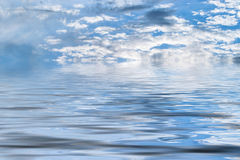 Clouds over water. White clouds over a body of water Stock Photo