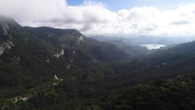 Aerial view in motion of the clouds and valley in the mountains on Adam`s Peak in Sri Lanka. Clouds pass over the settlement with the temple, which is located stock video