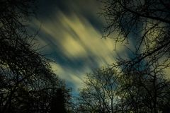 Clouds passing in the moon light by over a forest and on a night sky full of stars Stock Photos