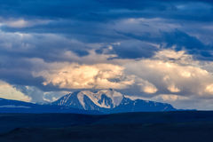 Clouds passing over mountain pinnacle in sunset light. In Altai royalty free stock photos