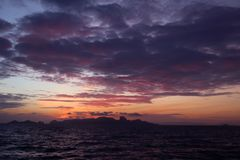 The clouds and purple red sky before sunrise in the ocean Stock Images