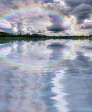 Clouds rainbow lake landscape. Summer nature landscape: shore with forest (trees) and sky with cumulus clouds and rainbow reflected in the lake (river) water Royalty Free Stock Images