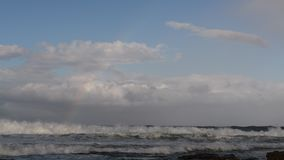 Clouds and rainbow in the sky over the ocean. South Africa. Mossel bay