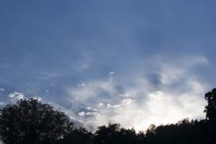 Clouds and Rays. Sun rays coming off clouds in a beautiful blue sky stock photo