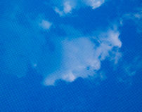 Clouds reflccting on calm water. The reflection of white summer clouds, on the surface of a swimming pool Stock Photography