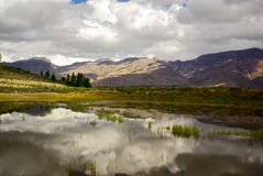 Clouds reflect in clear mountain lake in africa Royalty Free Stock Photography