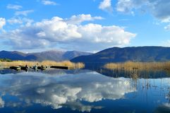 Clouds reflected in a blue lake Stock Images
