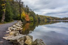 Clouds are reflected in a calm Minnewaska Lake in Orange County, NY, surrounded by bright fall foliage on a partly cloudy day. Clouds are reflected in a calm royalty free stock photo