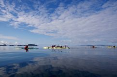 Clouds reflected in glassy ocean as kayakers paddle in the outer islands of th Great Bear Rain Forest. Kayakers enjoy a morning paddle in calm seas of the outer stock photo