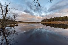 Clouds reflected in i calm lake in Sweden stock images