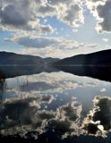 Clouds reflected in a lake before sunset Royalty Free Stock Photos