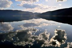 Clouds reflected in a lake before sunset. Still water and clouds' reflections in a lakescape view on Lake Prespes, a popular travel, vacation and trout fishing Stock Photography