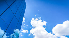 Clouds reflected in the many mirrored facets of a modern office. Building Stock Photo