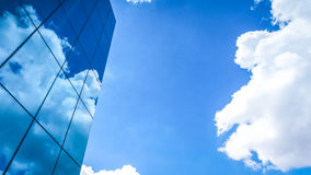Clouds reflected in the many mirrored facets of a modern office. Building Royalty Free Stock Photos