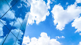 Clouds reflected in the many mirrored facets of a modern office. Building Royalty Free Stock Image