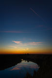 Clouds are reflected in river water. Evening landscape. Passenger plane in the night sky. Clouds are reflected in the river water. Evening landscape Royalty Free Stock Photography