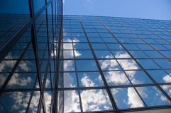 Clouds Reflected by Windows. Puffy white clouds reflected in glass of an office building - and then reflected back onto a 90 degree facing wall of windows royalty free stock photography