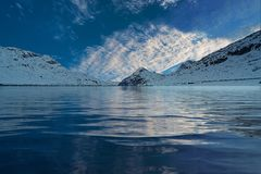 Clouds reflecting in alpine lake Stock Photo