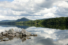 Clouds reflecting on a lake. Landscape in Norway including the reflection of the clouds on a lake Stock Photo