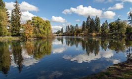 Clouds reflecting,Mirror Pond, Bend. Mirror pond in downtown Bend is almost perfectly still in this autumnal image of peace. Located on the Deschutes River it Royalty Free Stock Photography