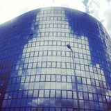 Clouds reflecting in modern office building stock image