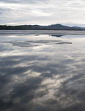 Clouds Reflecting Off Of Partially Frozen Lake. Clouds reflecting off of a partially frozen lake in Maine, during spring months. Mountains sit in the distant Royalty Free Stock Image
