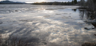 Clouds Reflecting On Partially Frozen Lake Stock Photography