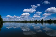 Clouds reflecting in the river Stock Images