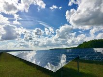 Clouds reflecting in solar photovoltaics panels field Royalty Free Stock Photo