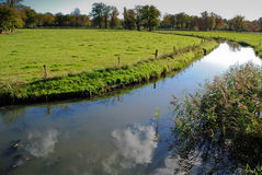Clouds reflecting in a streem. Clouds reflecting in a stream in the fields Stock Images