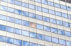 Clouds reflecting in windows of skyscraper Royalty Free Stock Image