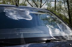 Clouds reflection on the car window. Modern car standing under the cloudy summer sky Royalty Free Stock Photo