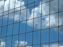Clouds Reflection in Modern Office Block Windows. Modern building with clouds reflecting in glass frontage royalty free stock images
