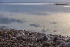 Clouds reflection at stony beach of Dead Sea Royalty Free Stock Photo
