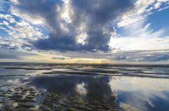 Clouds reflections in the still ocean from the beach, Bay of Sai Stock Photography